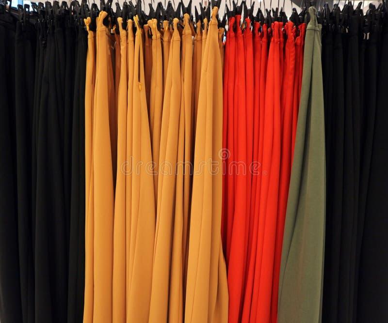 Kvinnors byxa i färgerna av vårsommarmode på en hängare i det bekläda lagret arkivfoto