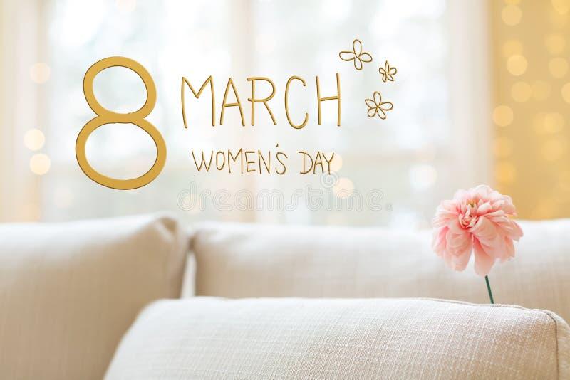 Kvinnors dagmeddelande med blomman i inre rumsoffa fotografering för bildbyråer