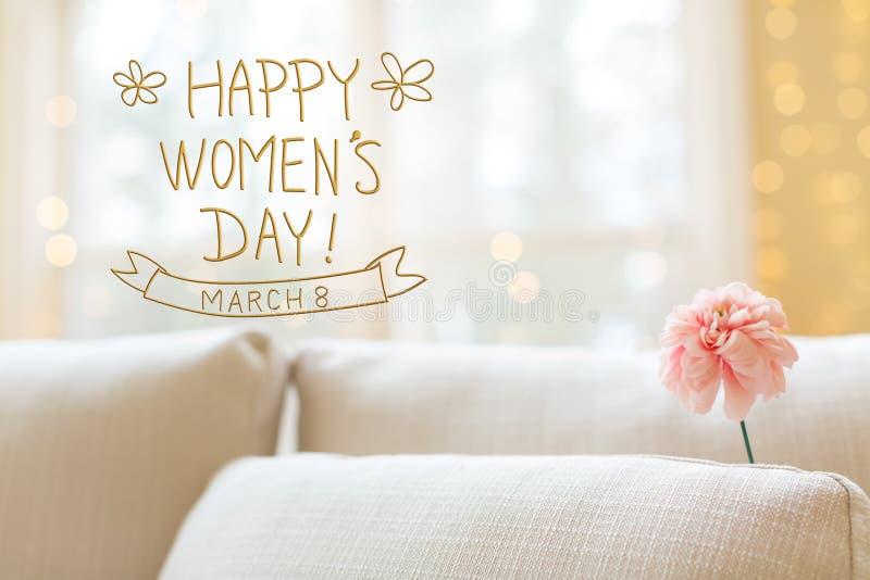 Kvinnors dagmeddelande med blomman i inre rumsoffa arkivfoton