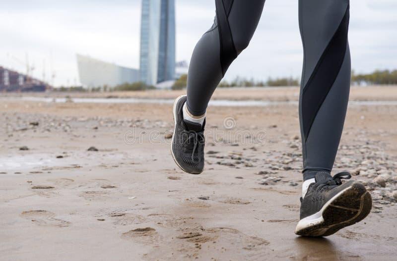Kvinnors fot i mörk damasker och svarta gymnastikskor på sanden som kör på våt sand, flicka som kör på stranden arkivfoton