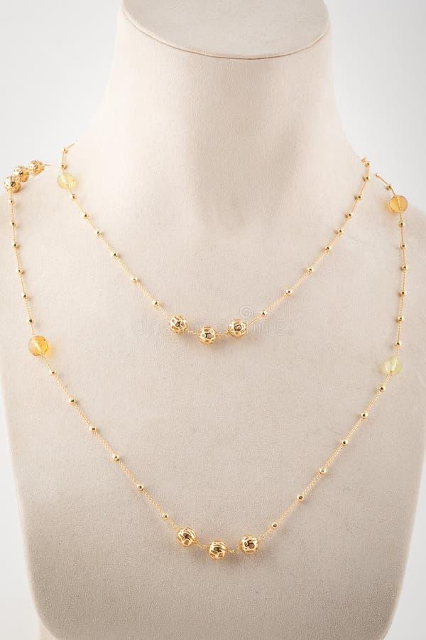 Kvinnors guld- dubbla kedja med pärlor, guld- stenar på den vita skyltdockan royaltyfri foto