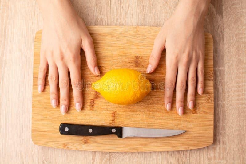 Kvinnors händer, kniv och citron på träskärbrädan royaltyfri foto