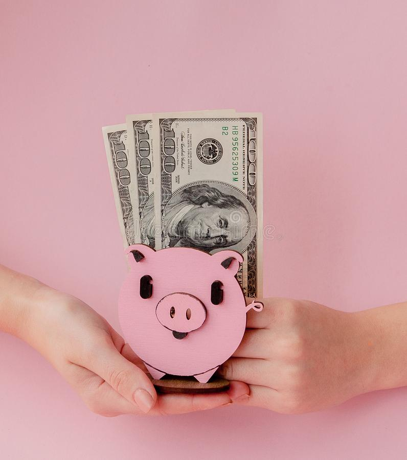Kvinnors händer som rymmer rosa piggybank- och dollarsedlar på rosa bakgrund arkivbild