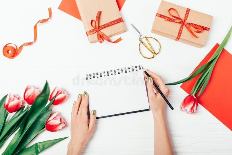 Kvinnors händer som skriver i tom anteckningsbok arkivbilder