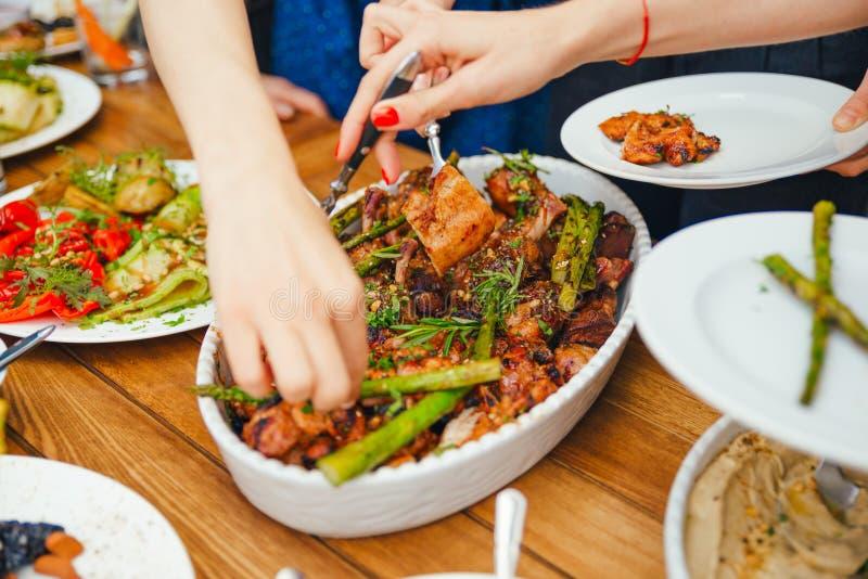Kvinnors händer traver sig ett mål i en platta av lunch Begreppet av näring bufferten Mat matställe Begreppet av att dela arkivfoto