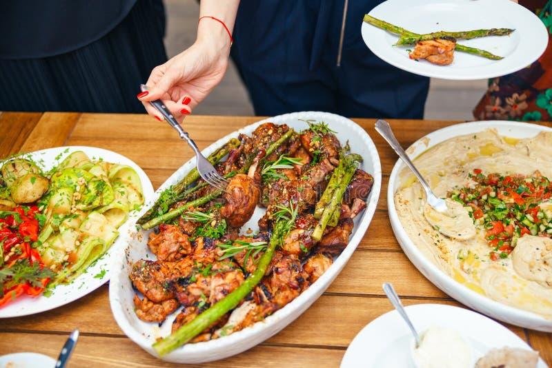 Kvinnors händer traver sig ett mål i en platta av lunch Begreppet av näring bufferten Mat matställe Begreppet av att dela royaltyfri foto