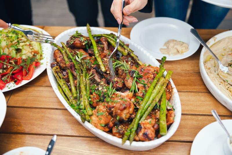 Kvinnors händer traver sig ett mål i en platta av lunch Begreppet av näring bufferten Mat matställe Begreppet av att dela royaltyfri bild