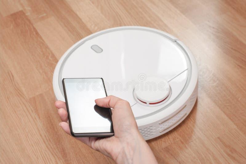 kvinnors hand genom att använda mobilen för att kontrollera vit robotic dammsugare modern smart reningsteknik royaltyfria bilder