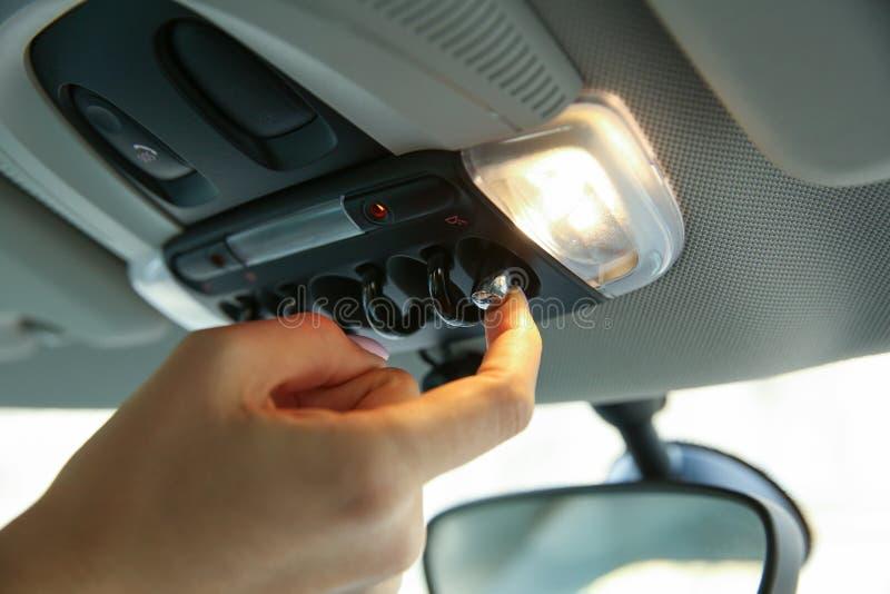 Kvinnors hand vänder på ljuset i bilen royaltyfri fotografi