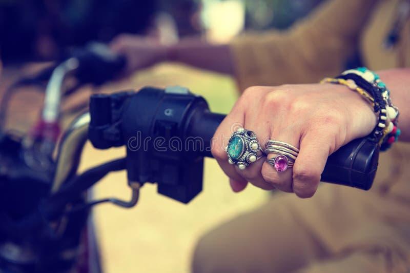 Kvinnors handnärbild med smycken på styret av en motorcykel royaltyfri foto
