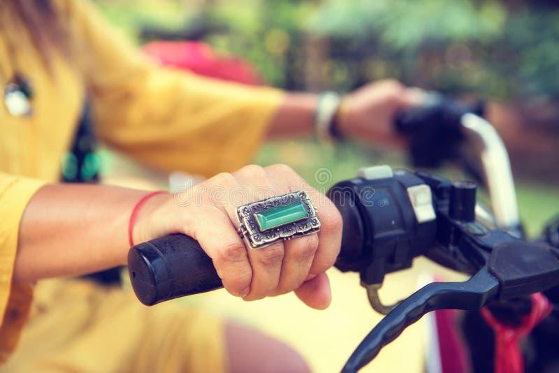 Kvinnors handnärbild med smycken på styret av en motorcykel arkivbild