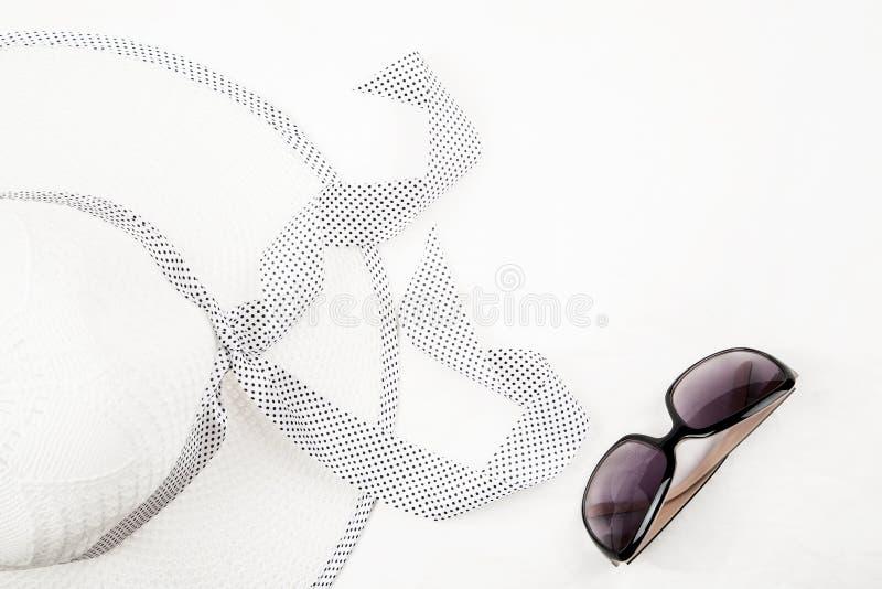 Kvinnors hatt och solglasögon på en vit bakgrund, bästa sikt, textutrymme fotografering för bildbyråer