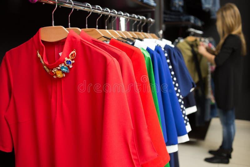 Kvinnors klänningar på hängare i ett återförsäljnings- shoppar royaltyfri bild