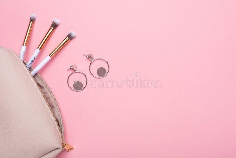 Kvinnors kosmetiska påse med makeupborstar och earringson en rosa bakgrund med kopieringsutrymme för din text royaltyfri fotografi