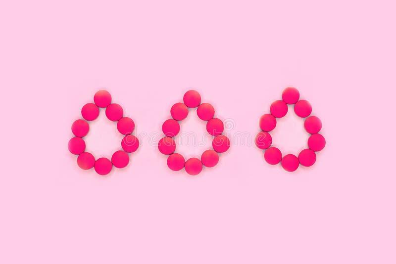 Kvinnors medicinskt begrepp för perioder som göras av minnestavlor eller piller i formen av bloddroppar på pastellfärgad rosa bak royaltyfria foton