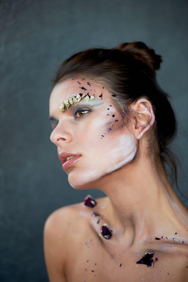 Kvinnors nyckelben På kroppen av målarfärgslaglängderna och kronbladen av de purpurfärgade blommorna Härlig thinness modell fotografering för bildbyråer