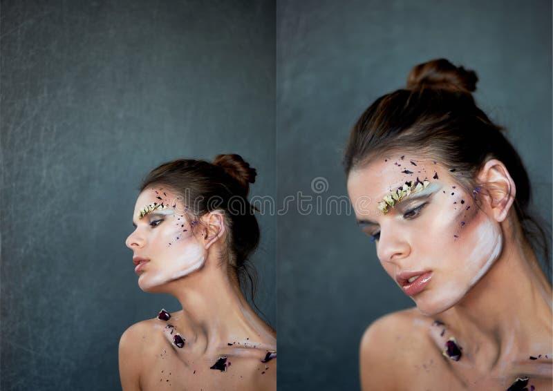 Kvinnors nyckelben På kroppen av målarfärgslaglängderna och kronbladen av de purpurfärgade blommorna Härlig thinness modell royaltyfri fotografi