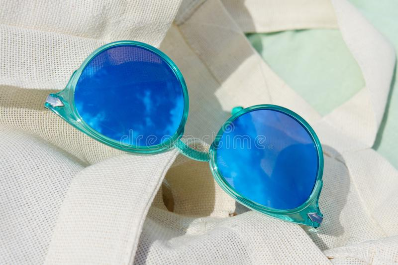 Kvinnors solglasögon med himmel och moln för reflekterande sommar som blå ligger på kanfas royaltyfri bild