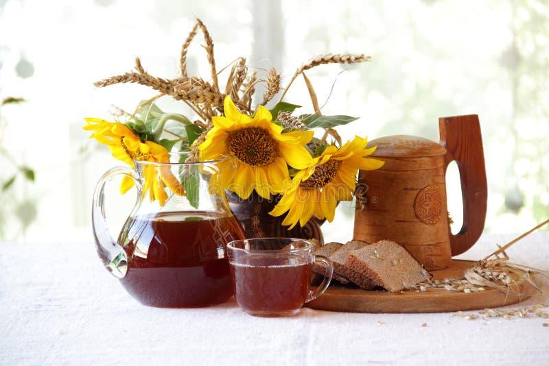 Kwaß (kvas) in einem hölzernen Becher, im Brot und in einem Blumenstrauß von Sonnenblumen stockfotografie