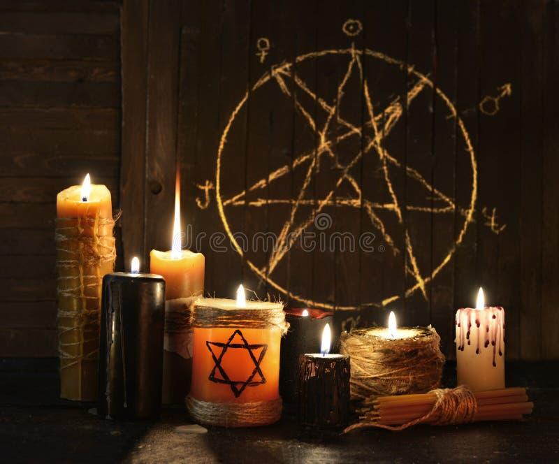 Kwade kaarsen tegen pentagramachtergrond stock foto