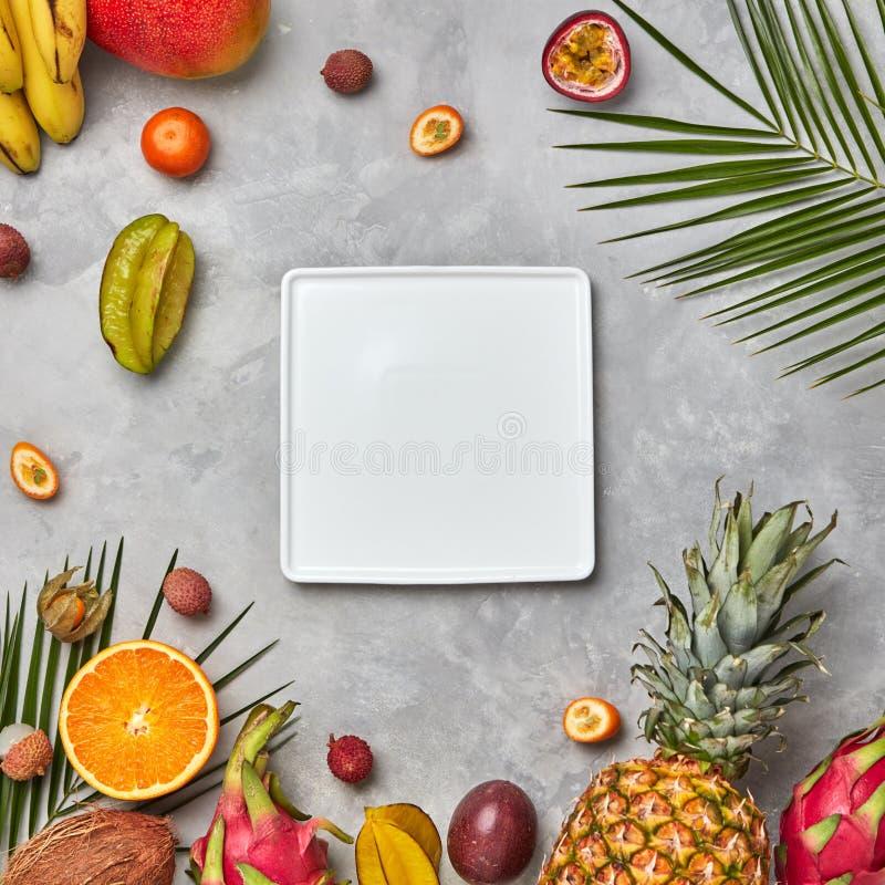 Kwadratowego bielu nalmium puści półkowi liście i soczyste tercet owoc, kumkva, pęcherzyca, pasyjna owoc, banan na szarości fotografia royalty free