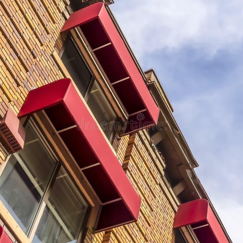 Kwadratowego budynku zewnętrzna uwypukla kamienna ściana z cegieł i czerwone markizy na okno zdjęcie stock