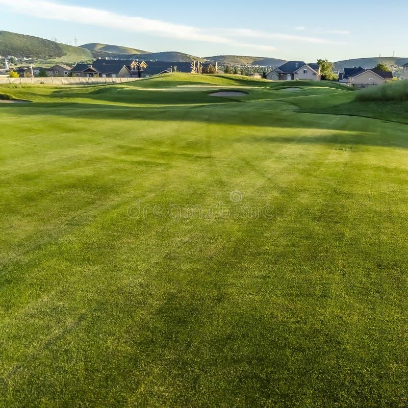 Kwadratowy farwater i bunkiery pole golfowe z w odległości domami i górą obrazy stock