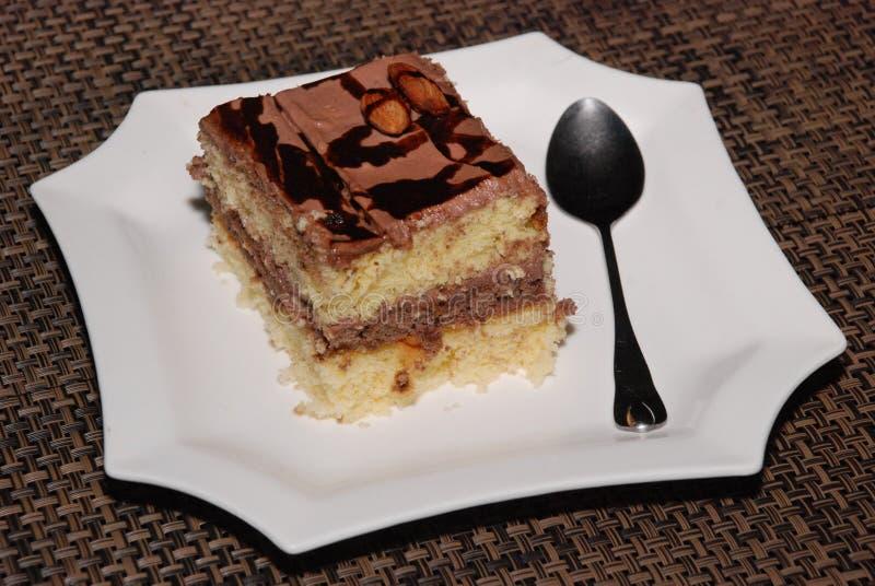 Kwadratowy kawałek tort z czekoladą i migdałem na białym talerzu zdjęcia royalty free
