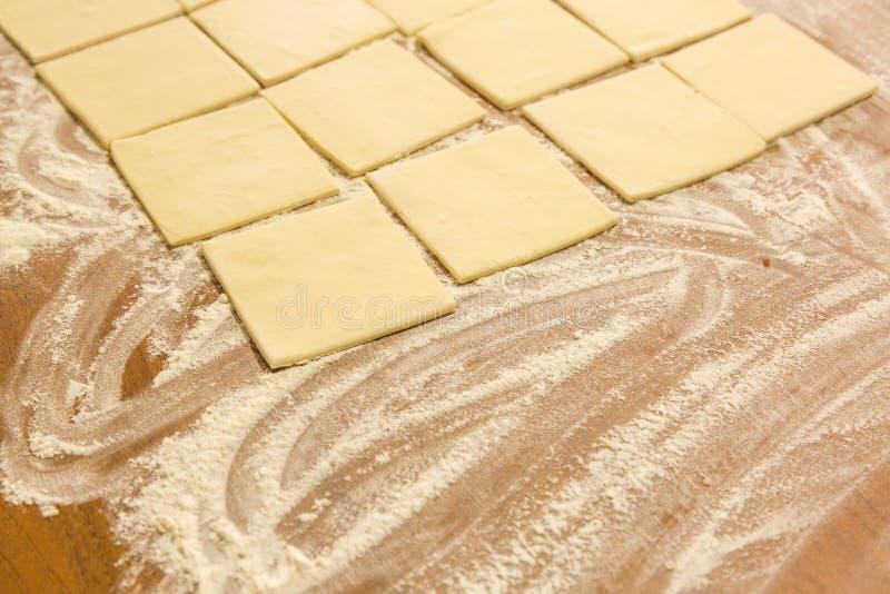 Kwadraty ciasto na stole z mąką obrazy stock
