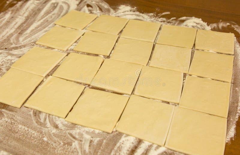 Kwadraty ciasto na stole z mąką zdjęcie royalty free