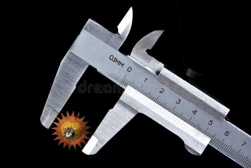 Kwaliteitscontrole die de grootte van een beugel-getand wiel meten Controle van het technische deel die van het toestel, aangewez stock afbeeldingen