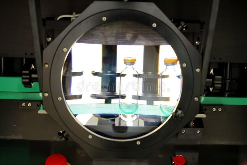 Kwaliteitscontroleflesjes voor injectie Het individu controleert flesje unde stock foto's