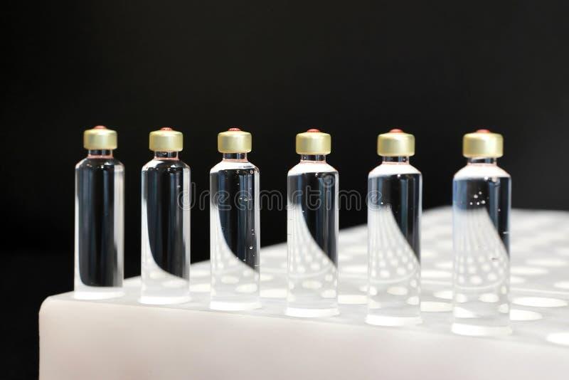 Kwaliteitscontroleflesjes voor injectie Het individu controleert flesje unde stock foto