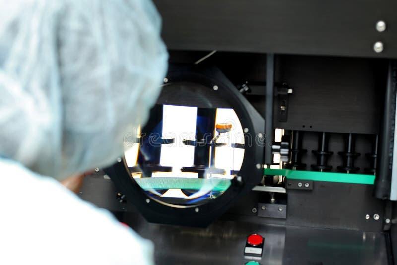 Kwaliteitscontroleflesjes voor injectie Het individu controleert flesje unde royalty-vrije stock fotografie