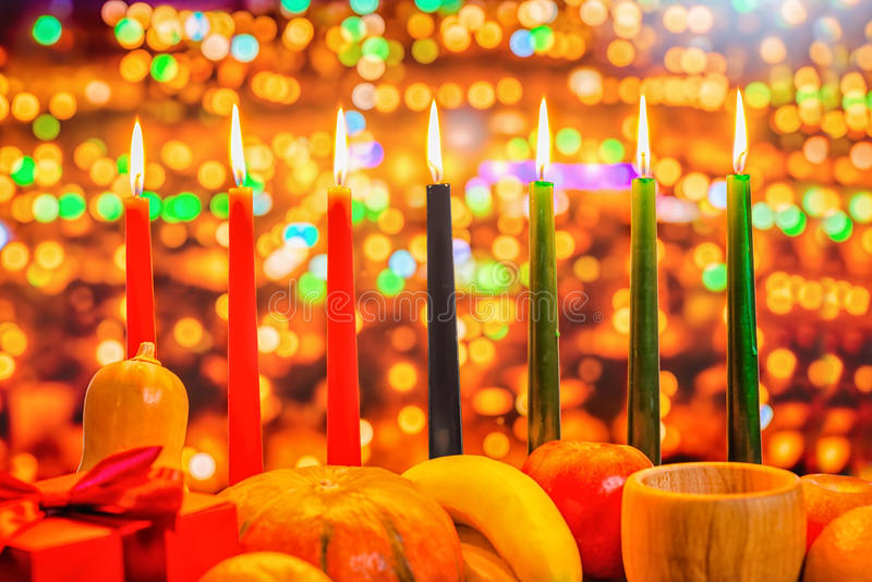 Kwanzaa celebration concept with seven candles red, black and gr. Een, gift box, pumpkin, bowl and fruit on light blur bokeh background, close up stock image