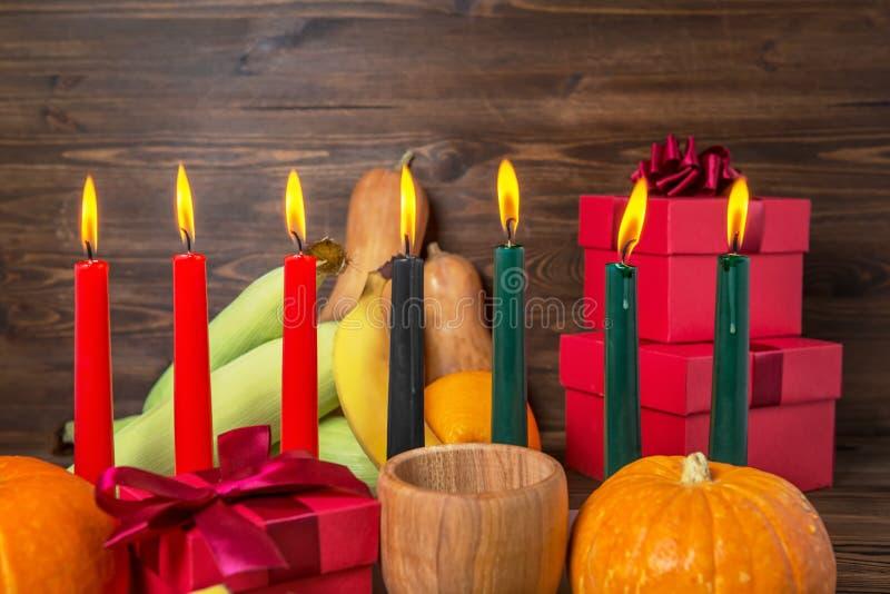 Kwanzaa feestelijk concept met het branden van kaarsen, giftdoos, pompoenen, oren van tarwe, druiven, korrels, banaan, kom en vru royalty-vrije stock fotografie