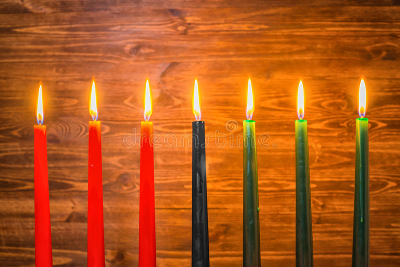 Kwanzaa festival concept with seven candles red, black and green. On wooden background, close up stock photos