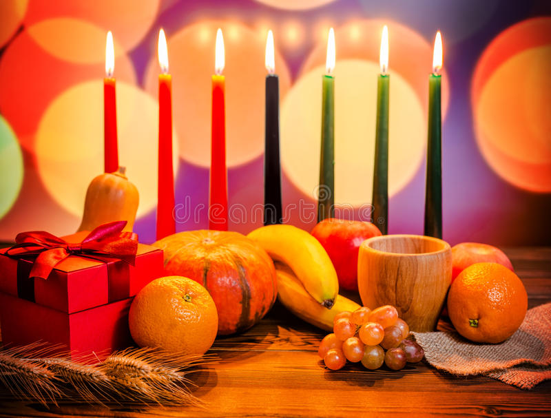 Kwanzaa festive concept with seven candles red, black and green, gift box, pumpkin, bowl and fruit on light blur bokeh background stock images