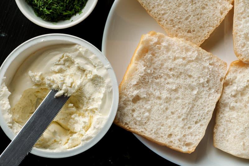 Kwark in kruik met mes en gesneden wit brood in een witte plaat, hoogste mening royalty-vrije stock afbeelding