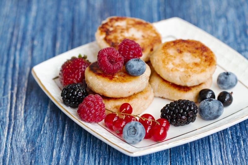 Kwarkpannekoeken, syrniki, gestremde melkfritters met verse bessen op blauwe achtergrond gezond delicatesseontbijt of royalty-vrije stock afbeelding