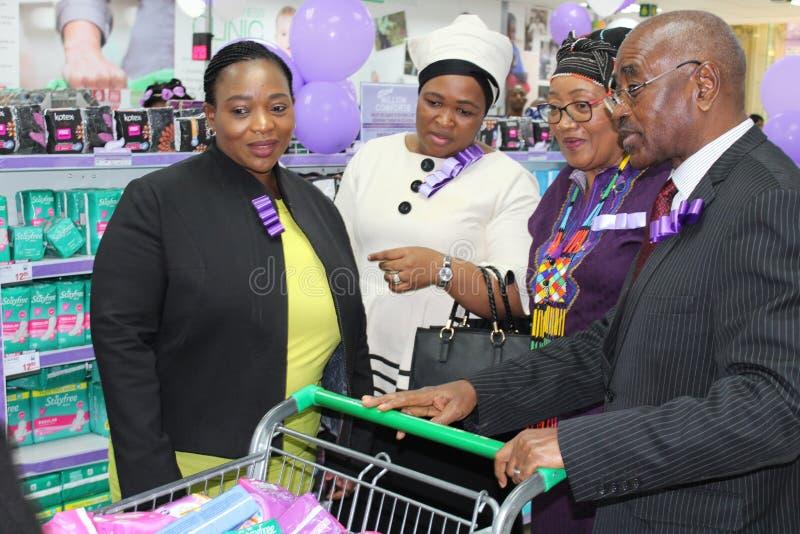 KwaZulu Natal Premier met hoogste vrouwen MECs en zijn presidentsvrouw die sanitaire stootkussens kopen helpen slechte meisjes in stock fotografie