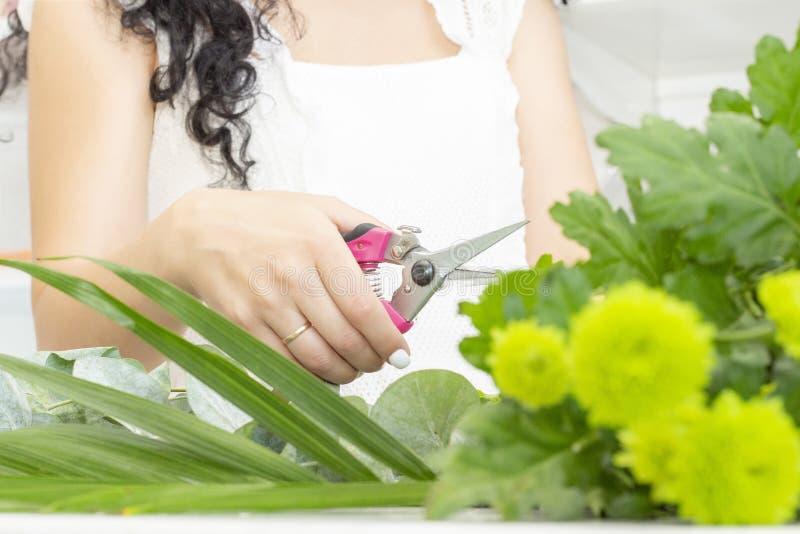 Kwiaciarni dziewczyna pracuje w kwiatu sklepie Miękcy cienie świezi wiosna kwiaty, zawijający w dekoracyjnym papierze Floristry b zdjęcia royalty free