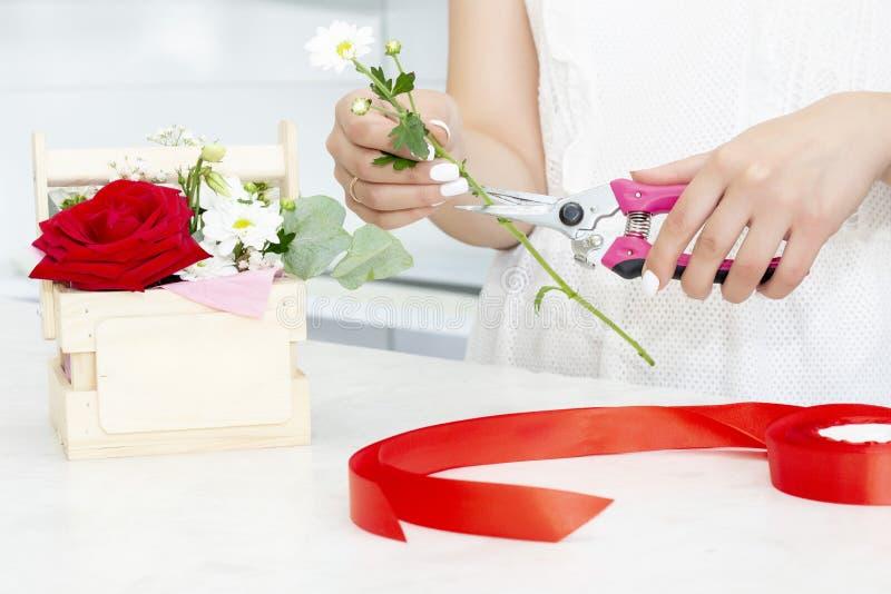 Kwiaciarni dziewczyna pracuje w kwiatu sklepie Miękcy cienie świezi wiosna kwiaty, zawijający w dekoracyjnym papierze Floristry b obraz royalty free