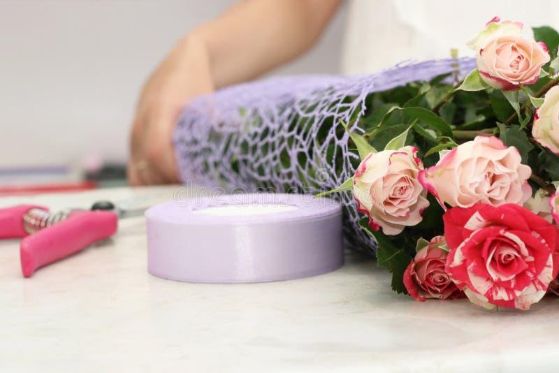 Kwiaciarni dziewczyna pracuje w kwiatu sklepie Miękcy cienie świezi wiosna kwiaty, zawijający w dekoracyjnym papierze Floristry b zdjęcie stock