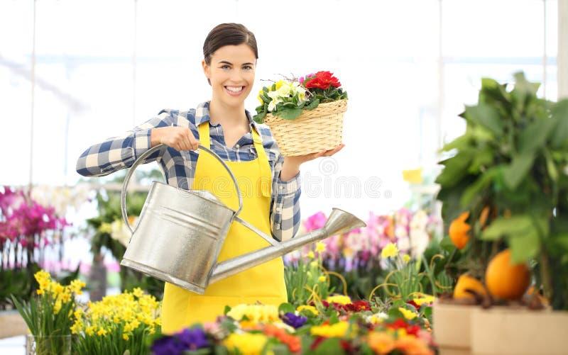 Kwiaciarni kobieta ono uśmiecha się z podlewanie puszką i łozinowymi koszykowymi kwiatami obraz stock