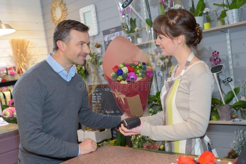 Kwiaciarnia i klient uzupełnia sprzedaż zdjęcia royalty free