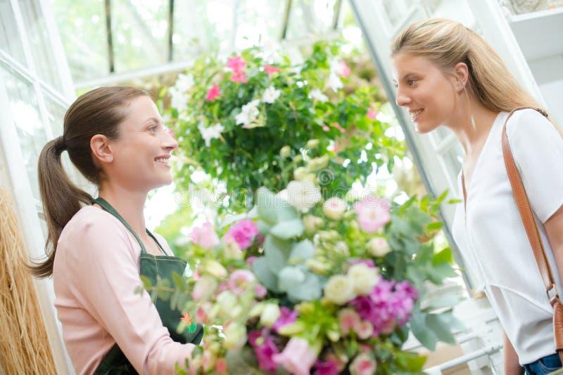 Kwiaciarnia stojąca z żeńskim klientem fotografia stock
