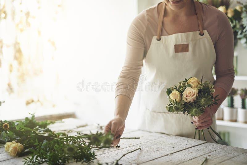 Kwiaciarnia układa bukiet róże w jej kwiatu sklepie obrazy royalty free
