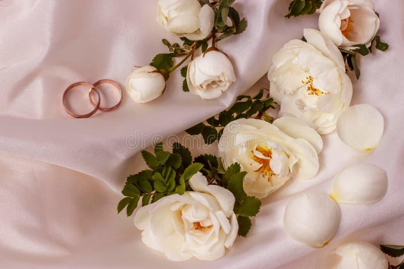 Kwiat różane i Złote białe dzikie obrączki ślubne na biel perle barwią tkaninę zdjęcia royalty free