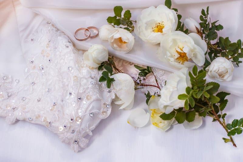 Kwiat różane i Złote białe dzikie obrączki ślubne na biel perle barwią tkaninę zdjęcie stock